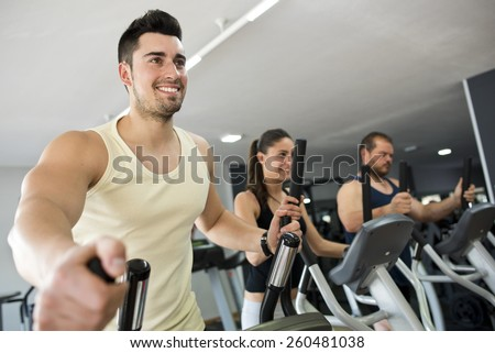 Active people at gym in elliptical bike, smiling man in focus.