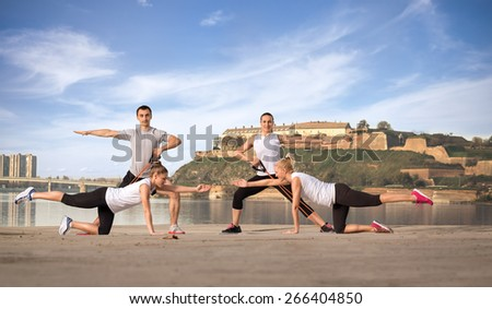 Active people doing workout outdoor next water - stock photo
