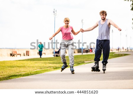 Active people modern couple exercise together and have fun. Relaxing hobby. Young people hold hands while rollerblading in park. - stock photo