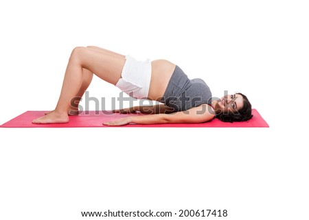 Active pregnant woman working out doing back press ups to strengthen and tone her muscles as she lies on a gym mat isolated on white - stock photo