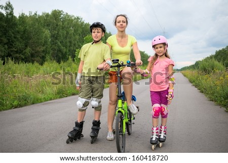 Active rest of the family of three with with roller skates and a bicycle