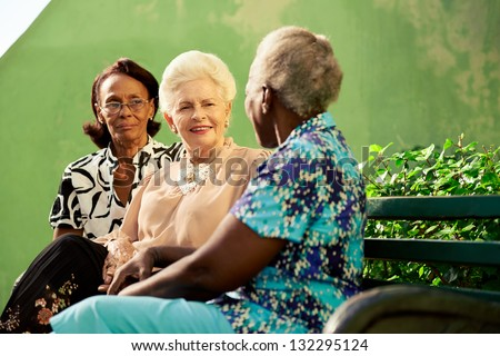 Active retired elderly women and free time, group of happy senior african american and caucasian female friends talking and sitting on bench in park - stock photo