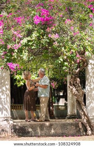 Active retired people having fun, happy old man and woman dancing latin american dance in patio - stock photo