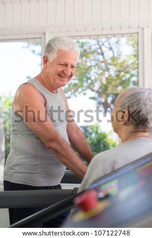 Active retired people, old man and woman talking and exercising in fitness gym