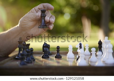 Active retired persons, hand of old man holding chess piece in park. Closeup shot, copy space - stock photo