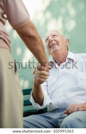 Active retirement, two old male friends talking and shaking hands on bench in public park