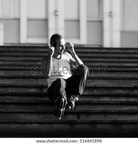 active roller in the park sitting on stairs - stock photo