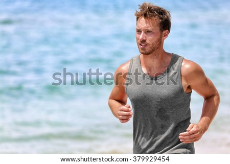 Active runner sweating running on beach. Handsome young male athlete wearing grey tank top for sweat wicking during intense cardio working on hot summer day with ocean background. - stock photo