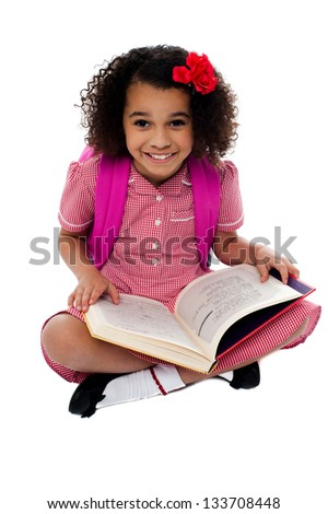 Active school kid with backpack seated on floor, reading a book. - stock photo