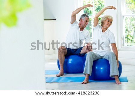 Active senior couple doing aerobics on ball at home - stock photo