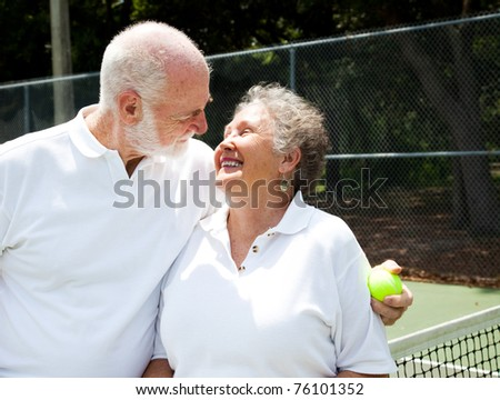 Active senior couple gets romantic on the tennis courts. - stock photo