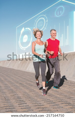 Active senior couple out for a jog against fitness interface - stock photo
