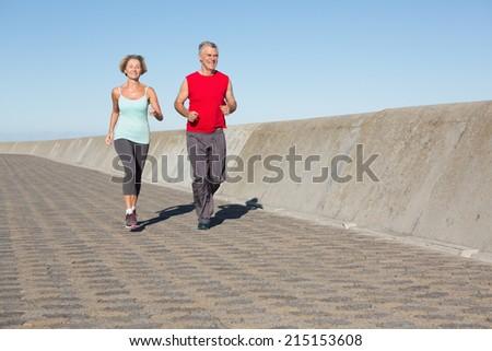 Active senior couple out for a jog on a sunny day - stock photo