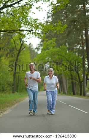 active senior couple run in summer forest - stock photo