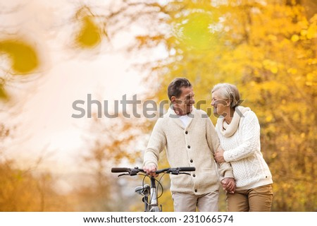 Active senior couple together enjoying romantic walk with bicycle in golden autumn park - stock photo
