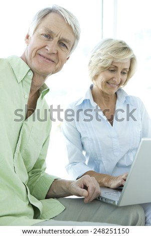 Active senior couple using laptop together