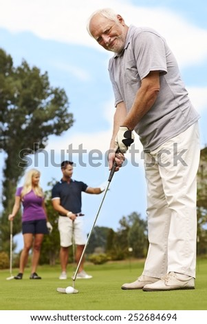 Active senior golfing, ready for holing. - stock photo