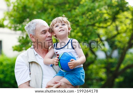 Active senior grandfather playing with little grandson ball in summer - stock photo