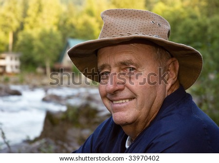 Active senior male fisherman with river close up with the river in the background.