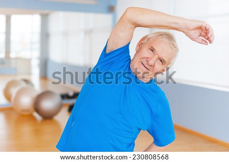 Active senior man. Cheerful senior man doing stretching exercises and smiling while standing indoors  - stock photo