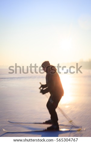 Active senior man cross-country skiing on huge snow meadow during lovely winter sunset (motion blurred image, color toned image)