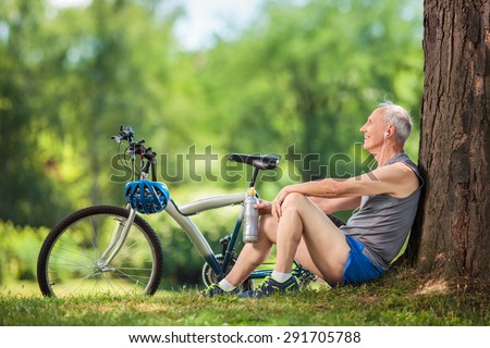 Active senior man listening to music on headphones seated by a tree in a park - stock photo