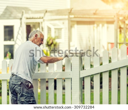 Active senior man painting a white picket fence with Instagram style filter - stock photo