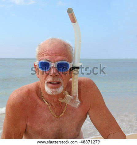 Active senior man ready to snorkel in the ocean - stock photo