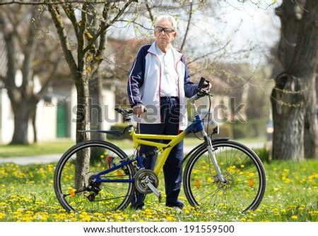 Active senior man resting after bike ride - stock photo