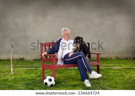 Active senior man with dog resting on bench - stock photo