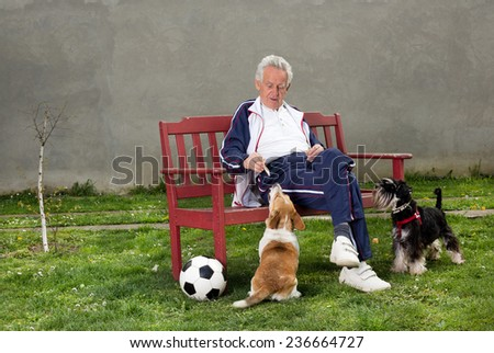 Active senior man with dogs resting on bench