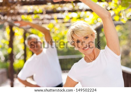 active senior woman exercising with husband outdoors - stock photo