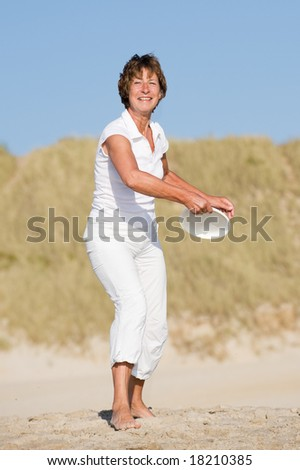 Active senior woman is tossing a frisbee at the beach - stock photo