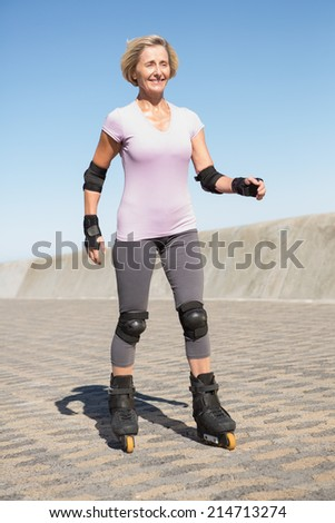 Active senior woman rollerblading on the pier on a sunny day - stock photo