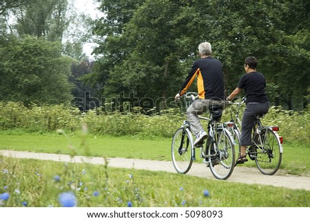 Active seniors biking in the park, from behind.