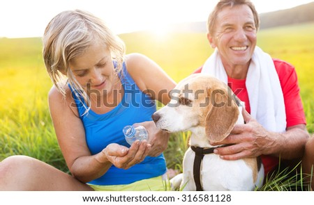 Active seniors having a break during their run outside in green nature - stock photo