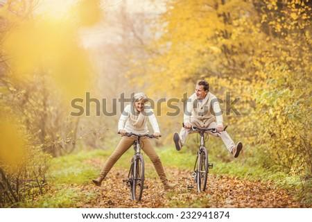 Active seniors on bikes in autumn nature