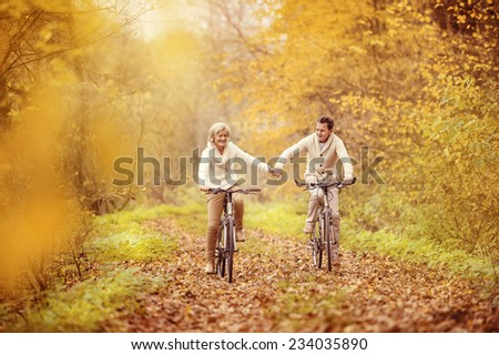 Active seniors riding bike in autumn nature. They relax outdoor. - stock photo