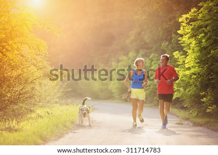 Active seniors running with their dog outside in green nature