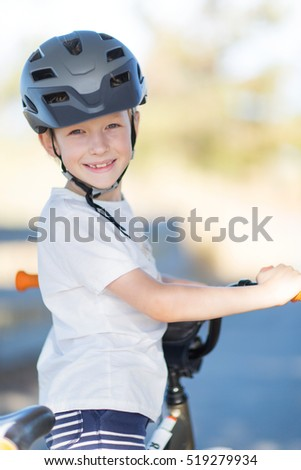 active smiling boy enjoying bike ride in the park