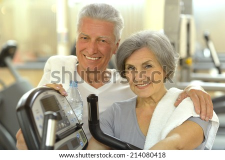 Active smiling  senior couple exercising in gym - stock photo