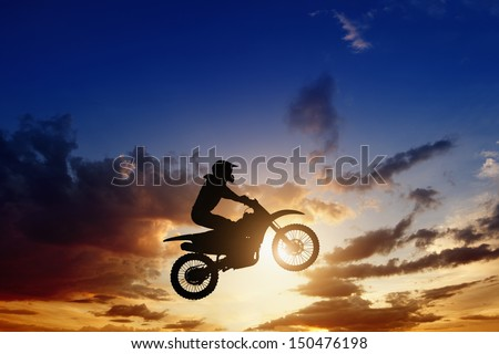 Active sports background - jumping motorcycle rider silhouette, beautiful sunset - stock photo