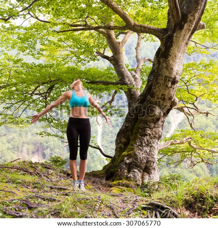 Active sporty girl raising arms inhaling fresh air, feeling  relaxed and free in beautiful natural environment. . Concept of natural, active, healthy, lifestile. - stock photo