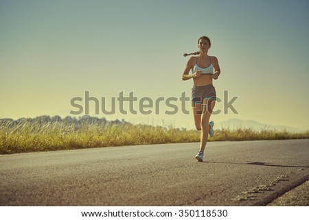Active sporty woman in summer sportswear running, sprinting on a road at sunrise or sunset. Health care, body care, healthy lifestyle, willingness concept. Toned color edit. - stock photo