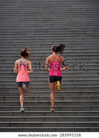 active sporty women working out running up stairs outdoors for morning workout - stock photo