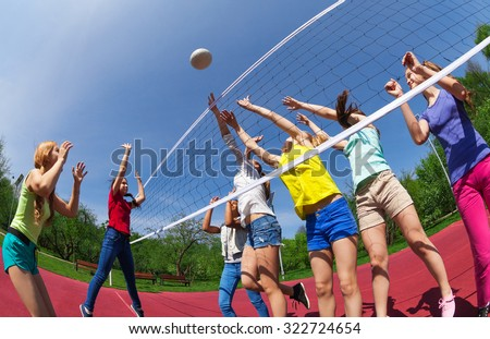 Active teenagers playing volleyball on the game court together outside during summer sunny day - stock photo