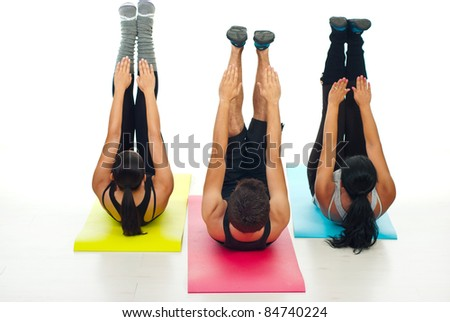 Active three people sitting on colorful mats and workout - stock photo