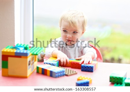 Active toddler girl building house from plastic blocks sitting next to a big window