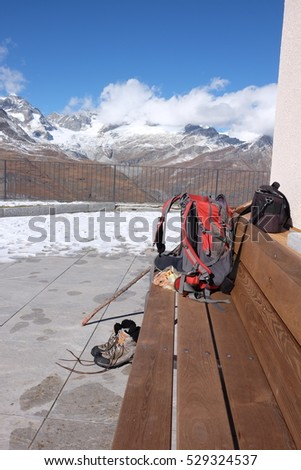 active tourist attributes against mountain background: backpack, camera, boots, pole stick, solo trip, Matterhorn, Riffelberg, Switzerland