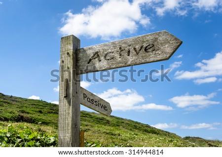 Active vs Passive. Directional Wooden Signpost - stock photo